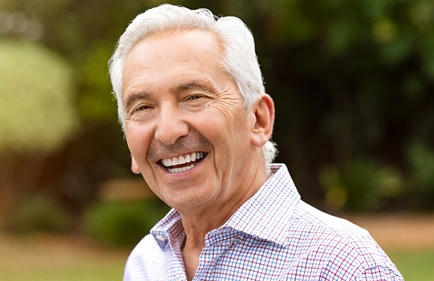 Older man with wrinkles smiling.
